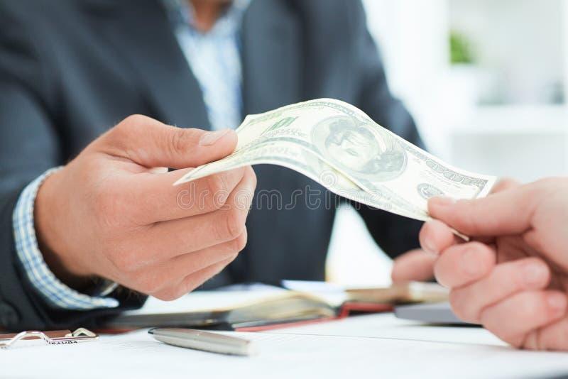 Κινηματογράφηση σε πρώτο πλάνο του businessperson που παίρνει τη δωροδοκία από το συνεργάτη στο ξύλινο γραφείο Ακριβώς παραδίδει  στοκ φωτογραφία