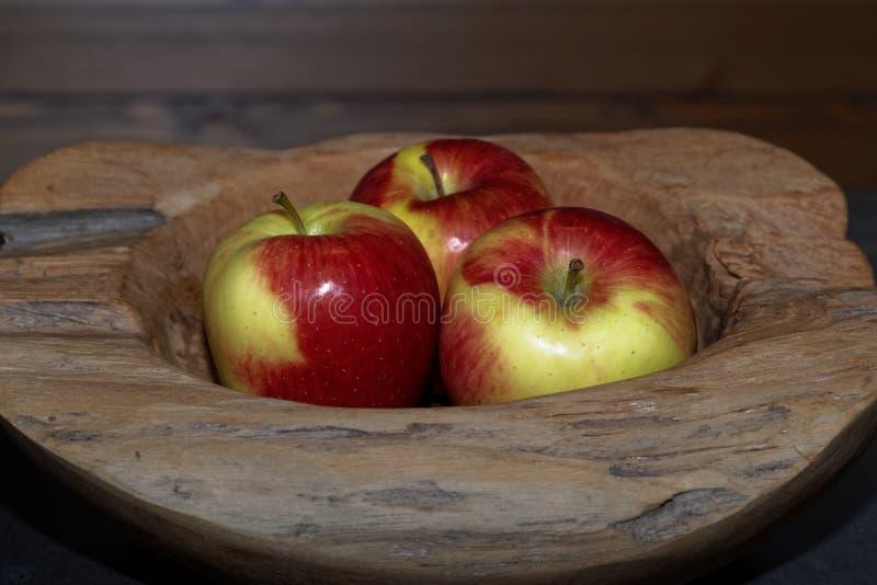 Κινηματογράφηση σε πρώτο πλάνο τριών μήλων σε ένα ξύλινο κύπελλο στοκ εικόνα