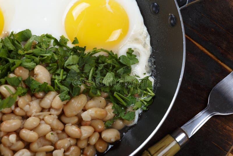 Κινηματογράφηση σε πρώτο πλάνο των ανακατωμένων αυγών με τα φασόλια και των πρασίνων σε ένα τηγανίζοντας τηγάνι Χορτοφάγα τρόφιμα στοκ φωτογραφίες
