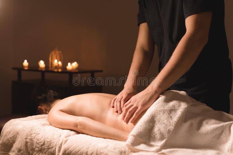 Κινηματογράφηση σε πρώτο πλάνο των αρσενικών χεριών Ο μασέρ τρίβει για τη μέση ενός νέου κοριτσιού Αποκατάσταση, ιατρική θεραπεία στοκ φωτογραφία με δικαίωμα ελεύθερης χρήσης