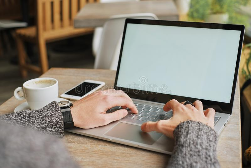 Κινηματογράφηση σε πρώτο πλάνο των αρσενικών χεριών που χρησιμοποιούν το σύγχρονο lap-top στο σπίτι ή της εσωτερικής, νέας επαγγε στοκ εικόνα