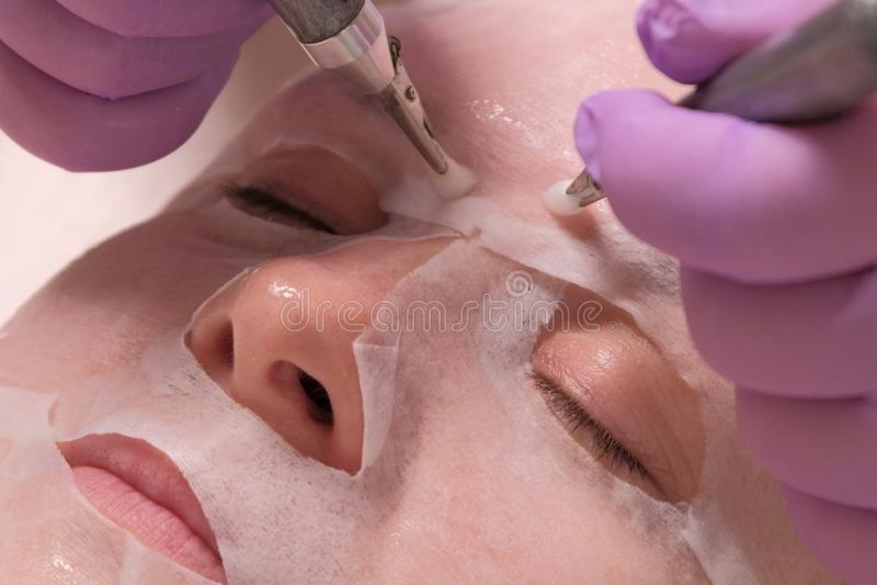Κινηματογράφηση σε πρώτο πλάνο των ηλεκτροδίων στα χέρια ενός beautician, σχετικά με το θηλυκό μάγουλο μέσω μιας μάσκας Γυναίκα π στοκ εικόνα με δικαίωμα ελεύθερης χρήσης