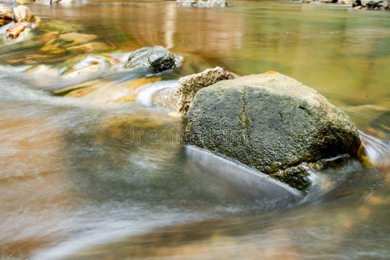 Κινηματογράφηση σε πρώτο πλάνο των μεγάλων πετρών που τίθενται στο νερό που εμποδίζει τη μετάβαση του νερού στο πάρκο στοκ εικόνες με δικαίωμα ελεύθερης χρήσης