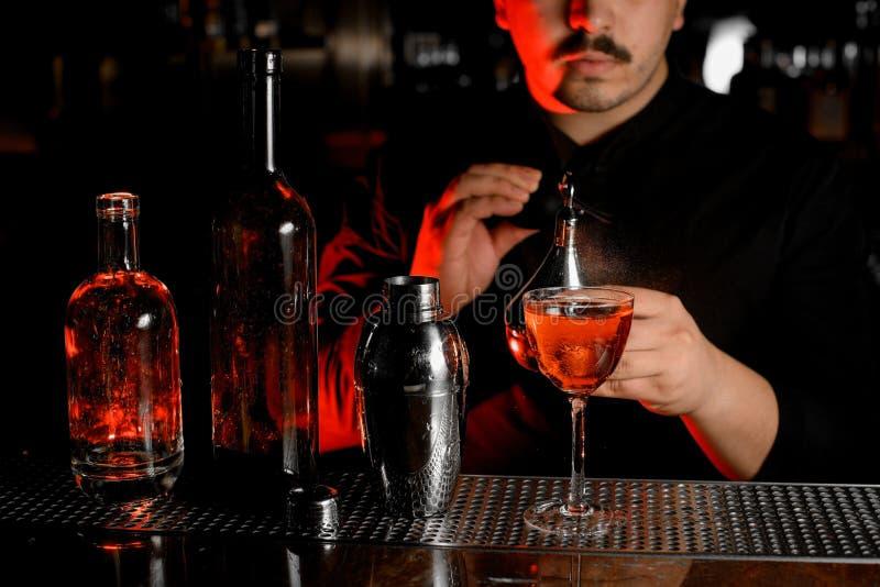 Κινηματογράφηση σε πρώτο πλάνο των μπουκαλιών, του δονητή, του κοκτέιλ και bartender με τον ψεκαστήρα στοκ φωτογραφίες με δικαίωμα ελεύθερης χρήσης