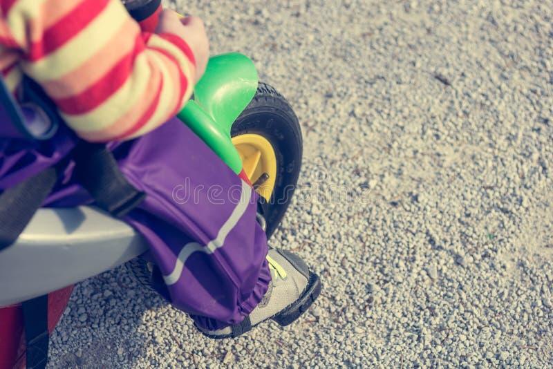 Κινηματογράφηση σε πρώτο πλάνο των ποδιών παιδιών που ωθούν ένα πεντάλι στο ποδήλατο στοκ φωτογραφία
