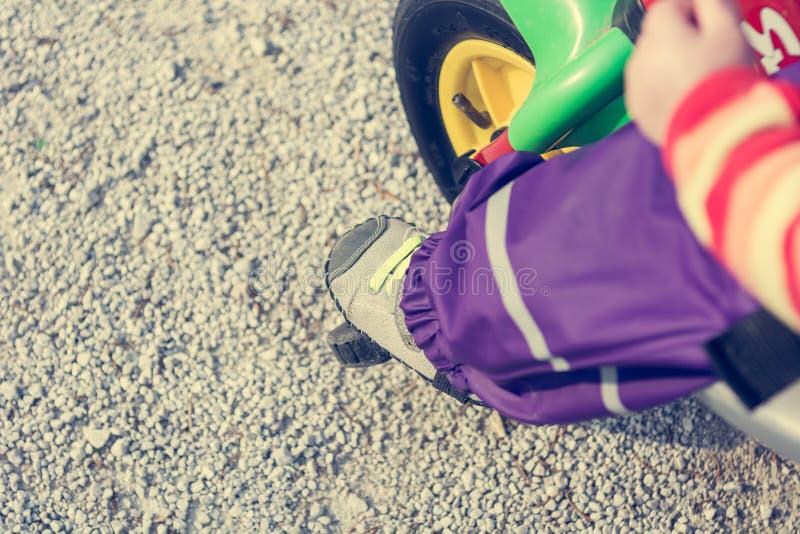 Κινηματογράφηση σε πρώτο πλάνο των ποδιών παιδιών που ωθούν ένα πεντάλι στο ποδήλατο στοκ εικόνες