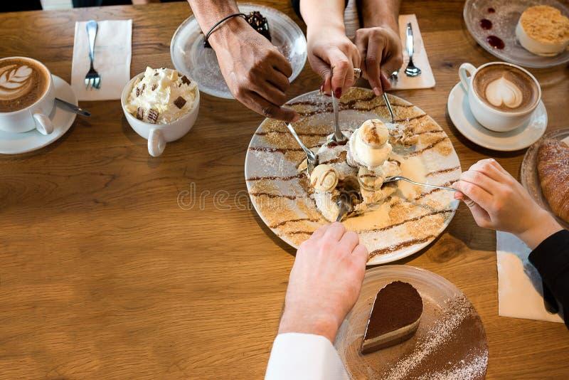 Κινηματογράφηση σε πρώτο πλάνο των πολυφυλετικών χεριών με τα επιδόρπια και των φλυτζανιών καφέ σε έναν καφέ στοκ φωτογραφίες