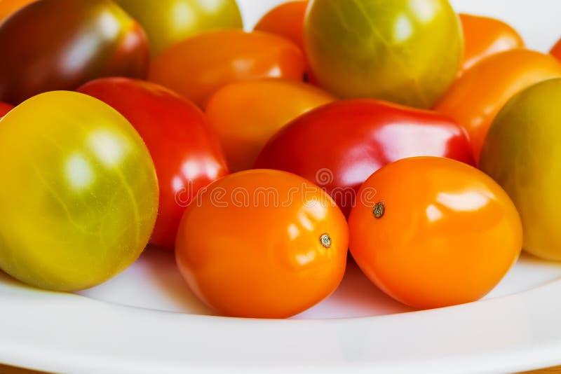 Κινηματογράφηση σε πρώτο πλάνο των πολύχρωμων ντοματών κερασιών σε ένα άσπρο πιάτο πορσελάνης Σωρός των κίτρινων, πορτοκαλιών και στοκ φωτογραφία