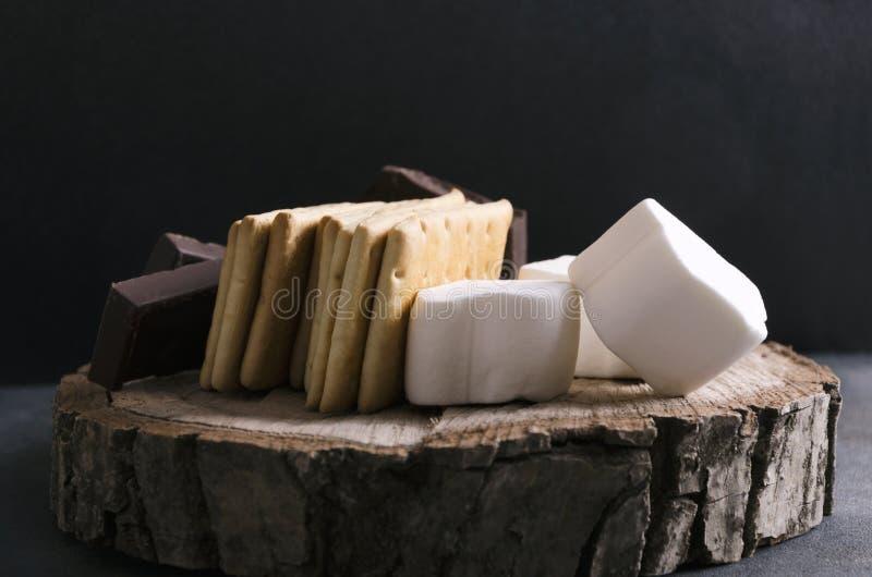Κινηματογράφηση σε πρώτο πλάνο των συστατικών για τα ήθη και έθιμα των νόστιμων s με marshmallows NAD σοκολάτας στον ξύλινο δίσκο στοκ φωτογραφίες