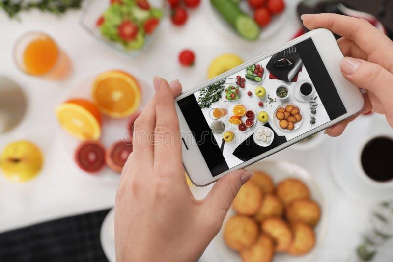 Κινηματογράφηση σε πρώτο πλάνο των τροφίμων blogger που φωτογραφίζουν το νόστιμο πρόγευμα με το κινητό τηλέφωνο στοκ εικόνα με δικαίωμα ελεύθερης χρήσης