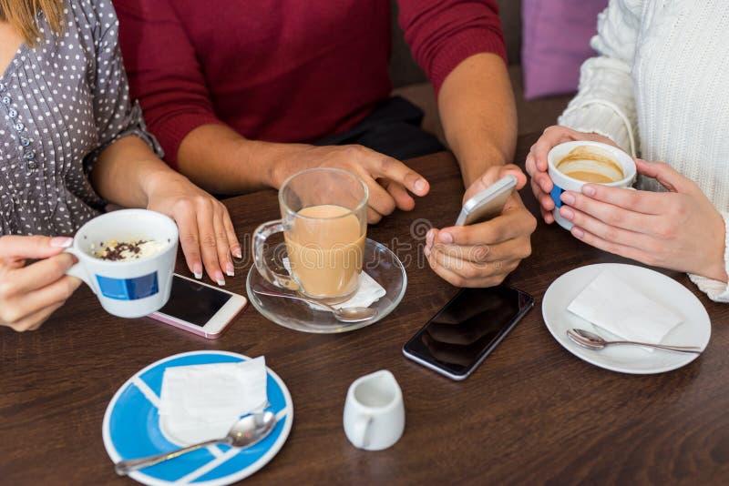 Κινηματογράφηση σε πρώτο πλάνο των φίλων που έχουν τον καφέ σε έναν καφέ στοκ εικόνες
