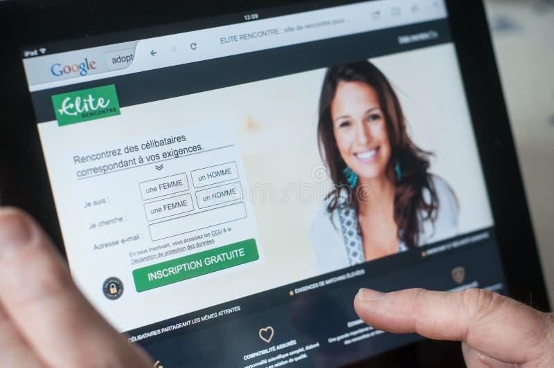 Κινηματογράφηση σε πρώτο πλάνο των χεριών γυναικών στην ελίτ που χρονολογεί την αρχική σελίδα του ιστοχώρου στην ταμπλέτα στοκ φωτογραφία