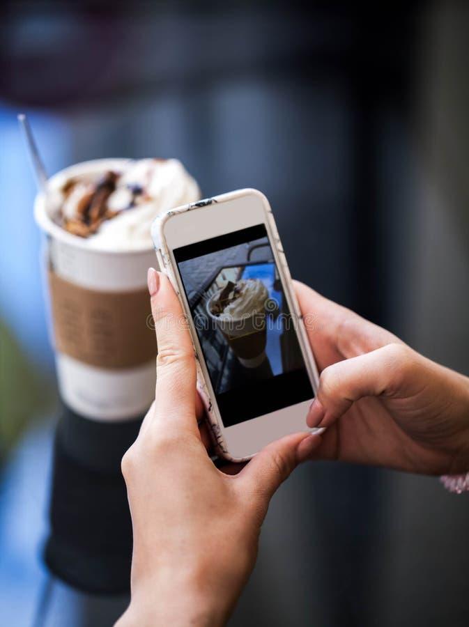 Κινηματογράφηση σε πρώτο πλάνο των χεριών γυναικών ` s που κάνουν τη φωτογραφία του γλυκού επιδορπίου στο κινητό τηλέφωνο καθμένο στοκ φωτογραφίες με δικαίωμα ελεύθερης χρήσης