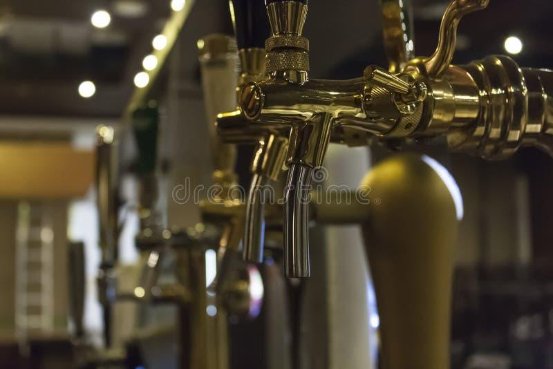 Κινηματογράφηση σε πρώτο πλάνο των χρυσών βρυσών μπύρας στοκ φωτογραφίες