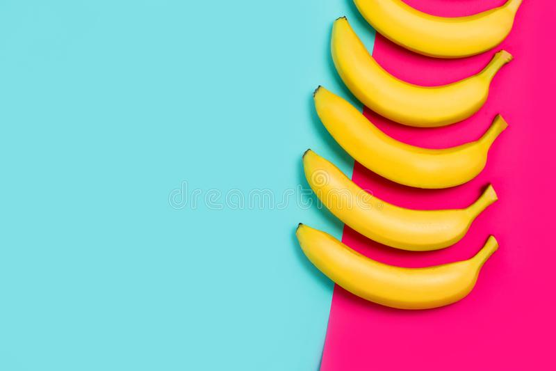 Κινηματογράφηση σε πρώτο πλάνο των ώριμων κίτρινων μπανανών σε έναν ζωηρόχρωμο του ρόδινου και μπλε β στοκ φωτογραφίες με δικαίωμα ελεύθερης χρήσης