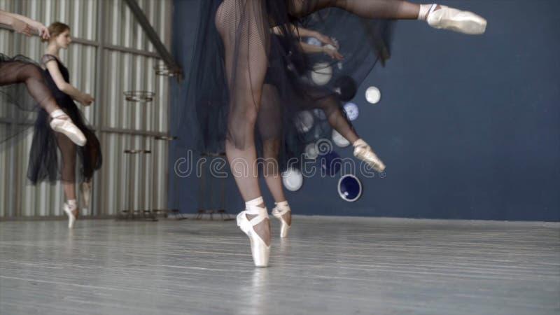 Κινηματογράφηση σε πρώτο πλάνο των ballerinas που χορεύει στα μαύρα φορέματα και το άσπρο παπούτσι pointe r Το Ballerinas προετοι στοκ εικόνες