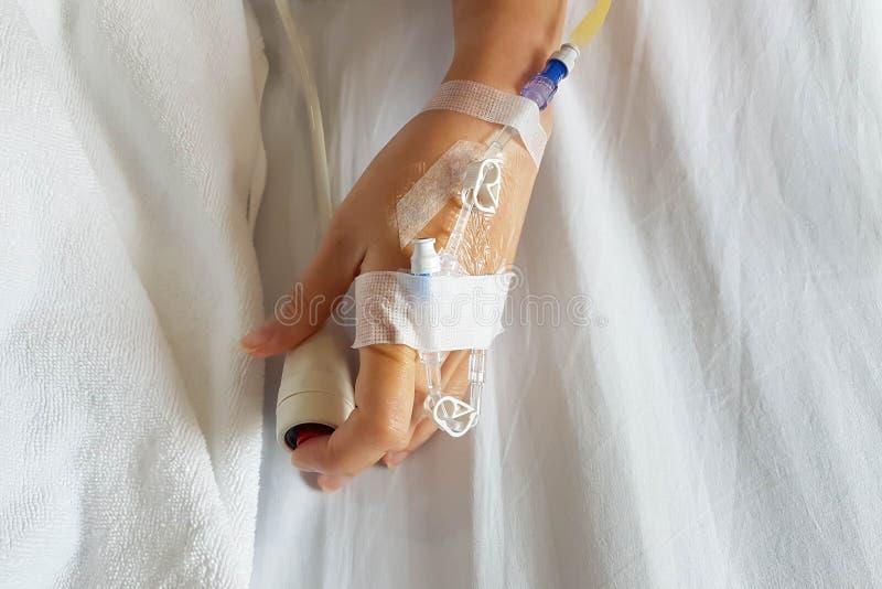 Κινηματογράφηση σε πρώτο πλάνο υπομονετικού χεριού με τη βελόνα έγχυσης και IV σωλήνα για το ενδοφλέβιο κουμπί έκτακτης ανάγκης έ στοκ φωτογραφία
