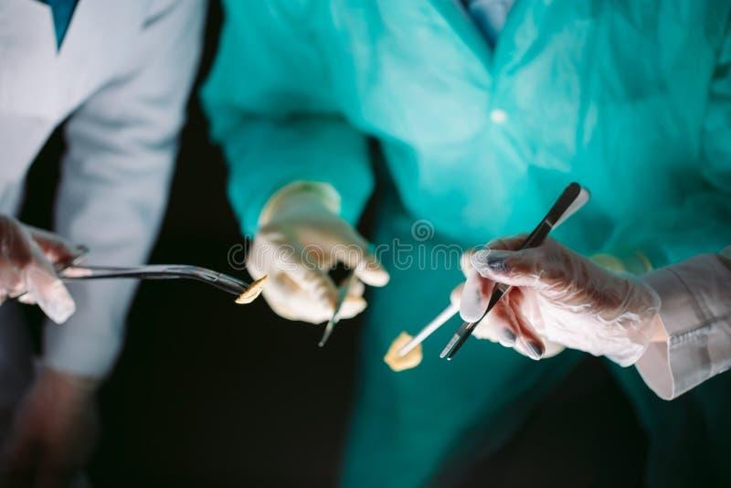 Κινηματογράφηση σε πρώτο πλάνο χεριών των χειρούργων που κρατούν τα ιατρικά όργανα Ο χειρούργος κάνει μια λειτουργία στοκ εικόνες