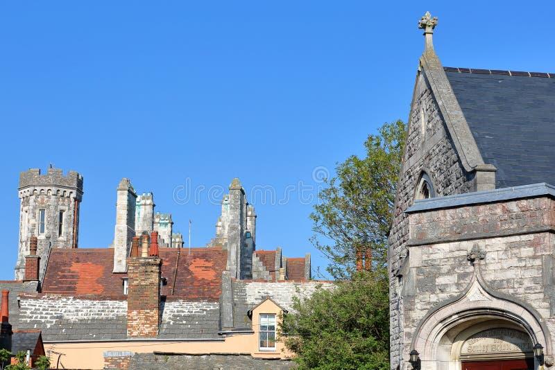 Κινηματογράφηση σε πρώτο πλάνο flagstone στις στέγες με τη μεθοδιστή εκκλησία Swanage στη δεξιά πλευρά και το βικτοριανό ξενοδοχε στοκ φωτογραφία