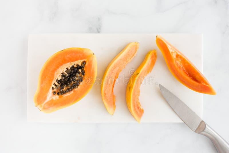 Κινηματογράφηση σε πρώτο πλάνο Papaya μισή και των φετών στο άσπρο μάρμαρο στοκ εικόνα με δικαίωμα ελεύθερης χρήσης