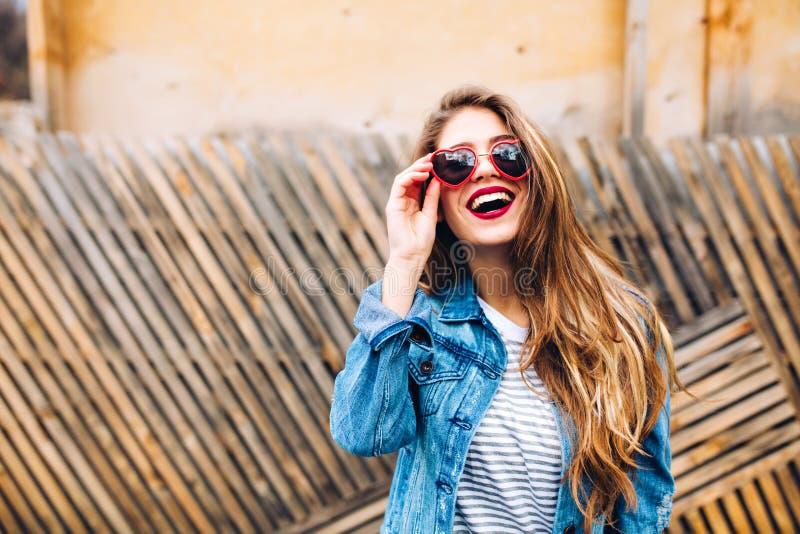 Κινηματογράφηση σε πρώτο πλάνο posrtait του θαυμάσιου θηλυκού προτύπου στο αναδρομικό σακάκι τζιν, που κρατά τα γυαλιά ηλίου και  στοκ φωτογραφία