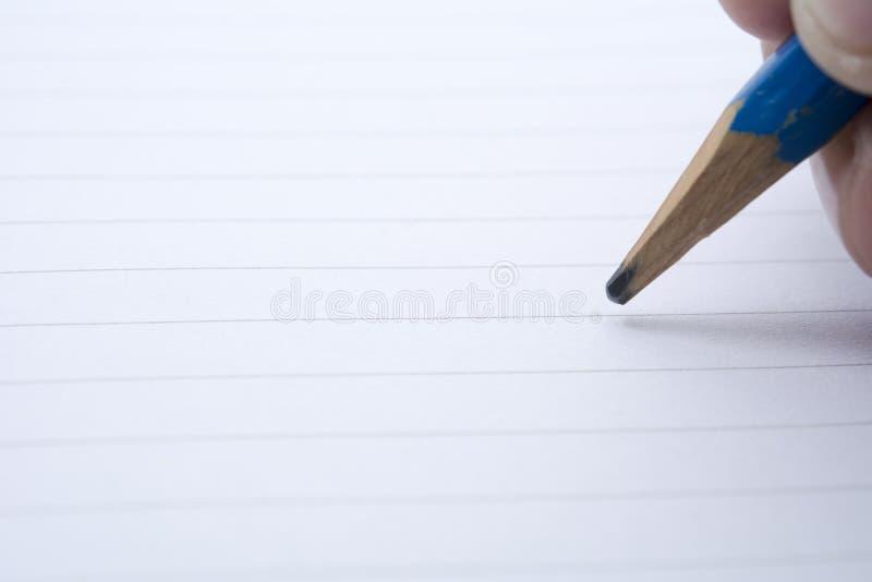 Κινηματογράφηση σε πρώτο πλάνο για το χέρι που επισύρει την προσοχή σε κενό χαρτί με το μολύβι στοκ εικόνα