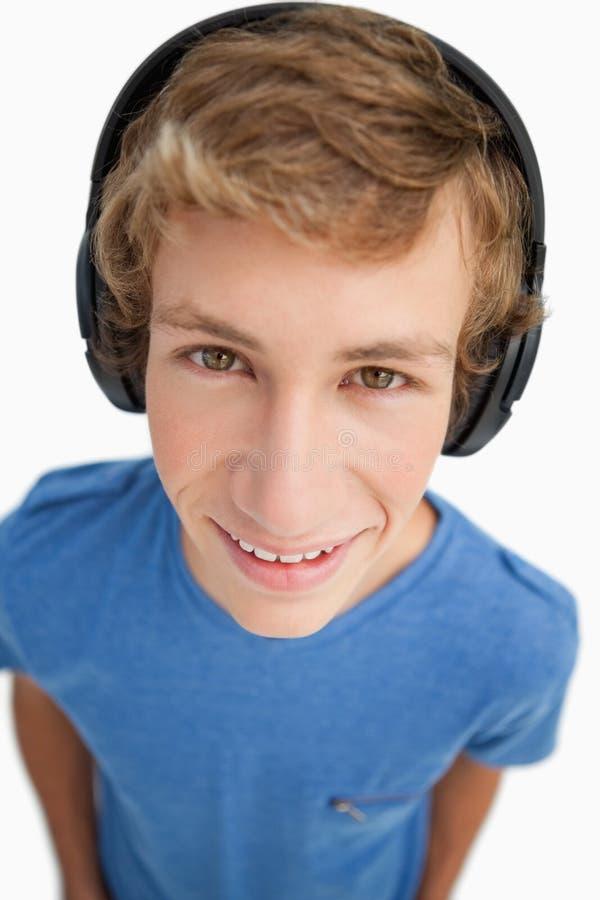 Κινηματογράφηση σε πρώτο πλάνο ενός άνδρα σπουδαστή που φορά τα ακουστικά στοκ εικόνα με δικαίωμα ελεύθερης χρήσης