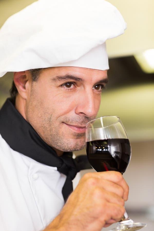 Κινηματογράφηση σε πρώτο πλάνο ενός αρσενικού αρχιμάγειρα που μυρίζει το κόκκινο κρασί στοκ εικόνα