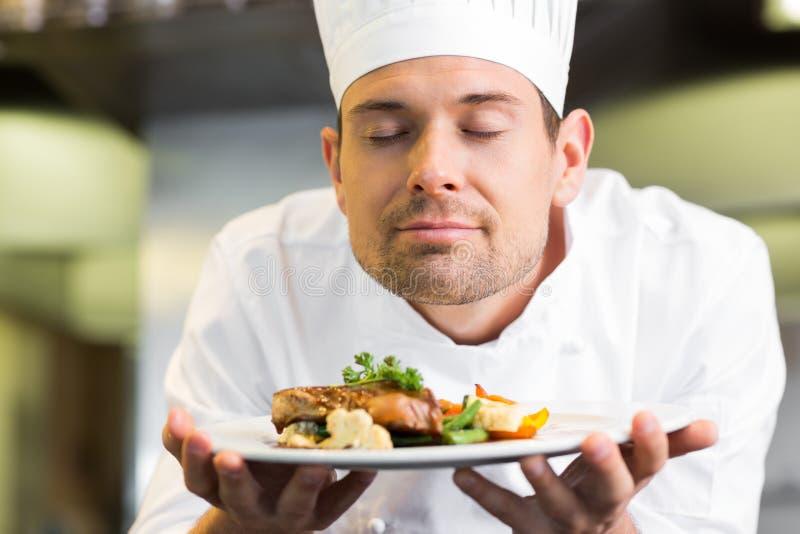 Κινηματογράφηση σε πρώτο πλάνο ενός αρχιμάγειρα με κλειστά τα μάτια μυρίζοντας τρόφιμα στοκ εικόνα