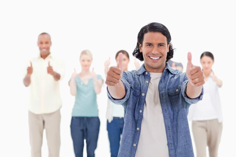 Κινηματογράφηση σε πρώτο πλάνο ενός ατόμου που χαμογελά με αντίχειρας-επάνω του με τους ανθρώπους πίσω στοκ εικόνες