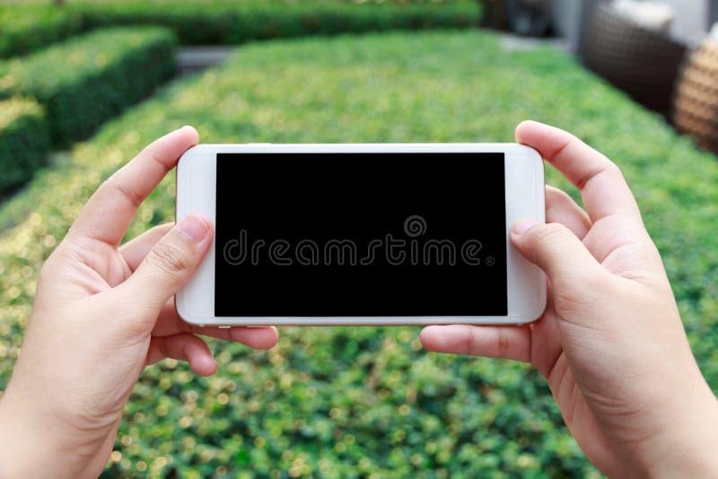 Κινηματογράφηση σε πρώτο πλάνο ενός βίντεο προσοχής κινητών τηλεφώνων εκμετάλλευσης χεριών γυναικών στοκ εικόνα με δικαίωμα ελεύθερης χρήσης