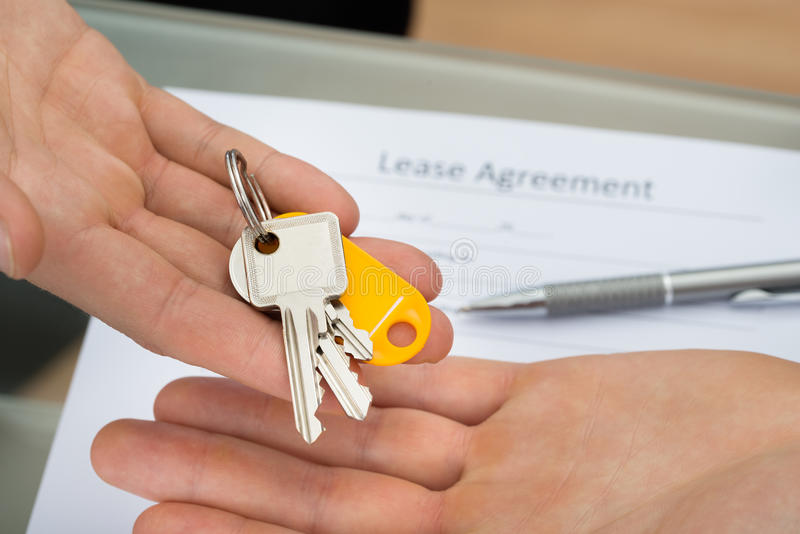 Κινηματογράφηση σε πρώτο πλάνο ενός προσώπου που δίνει το κλειδί στο άτομο στοκ εικόνα με δικαίωμα ελεύθερης χρήσης