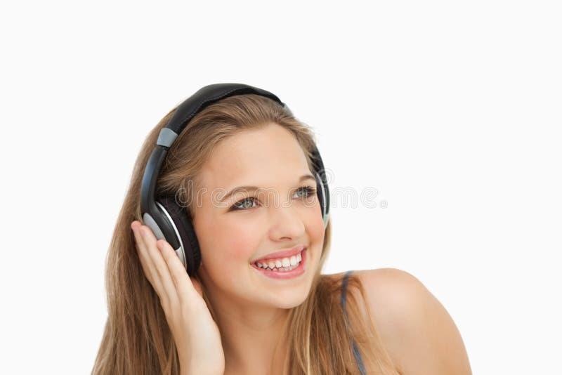 Κινηματογράφηση σε πρώτο πλάνο ενός χαμογελώντας σπουδαστή που φορά τα ακουστικά στοκ φωτογραφίες