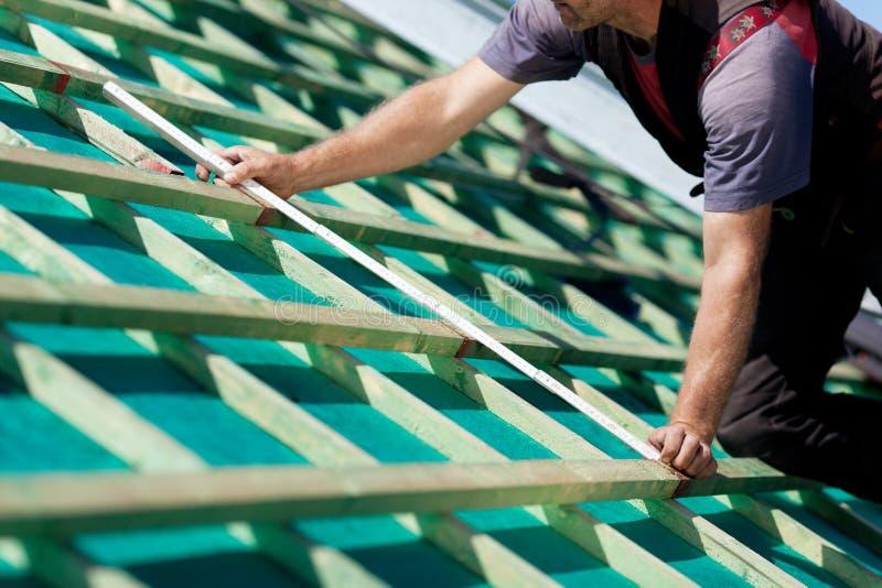 Κινηματογράφηση σε πρώτο πλάνο ενός roofer που μετρά τις ακτίνες στεγών στοκ εικόνα