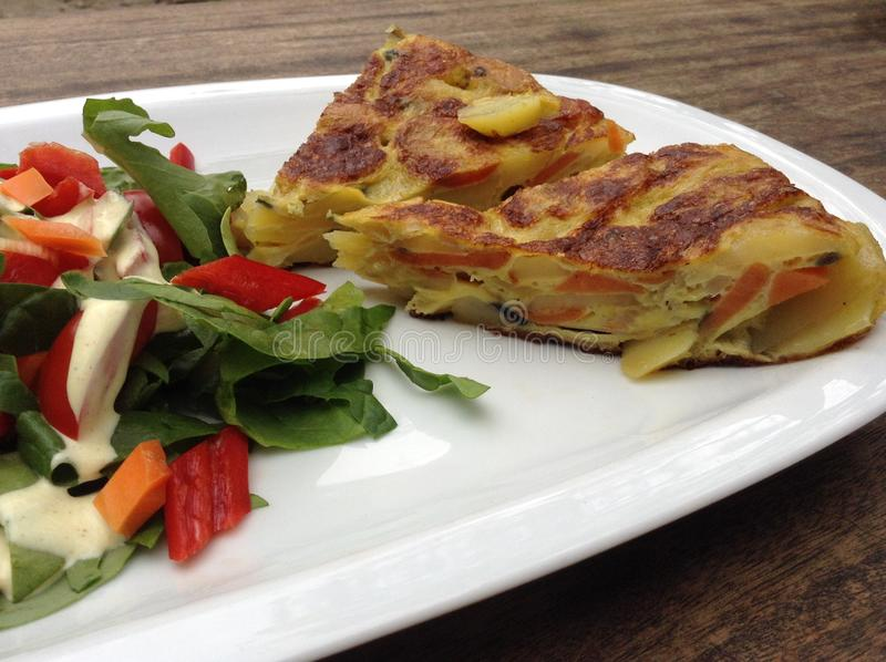 Κινηματογράφηση σε πρώτο πλάνο ισπανικό tortilla με τη σαλάτα στοκ φωτογραφία