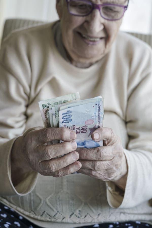 Κινηματογράφηση σε πρώτο πλάνο μιας ευτυχούς ανώτερης γυναίκας που μετρά τα τουρκικά τραπεζογραμμάτια λιρετών στοκ φωτογραφίες