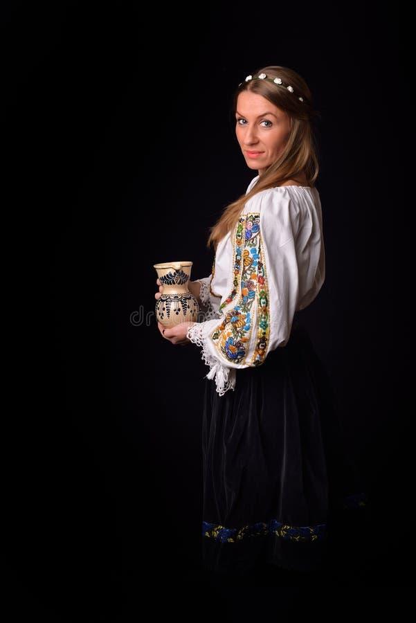 Κινηματογράφηση σε πρώτο πλάνο μιας νέας ρουμανικής γυναίκας που ντύνεται στο παραδοσιακό κοστούμι στοκ εικόνες
