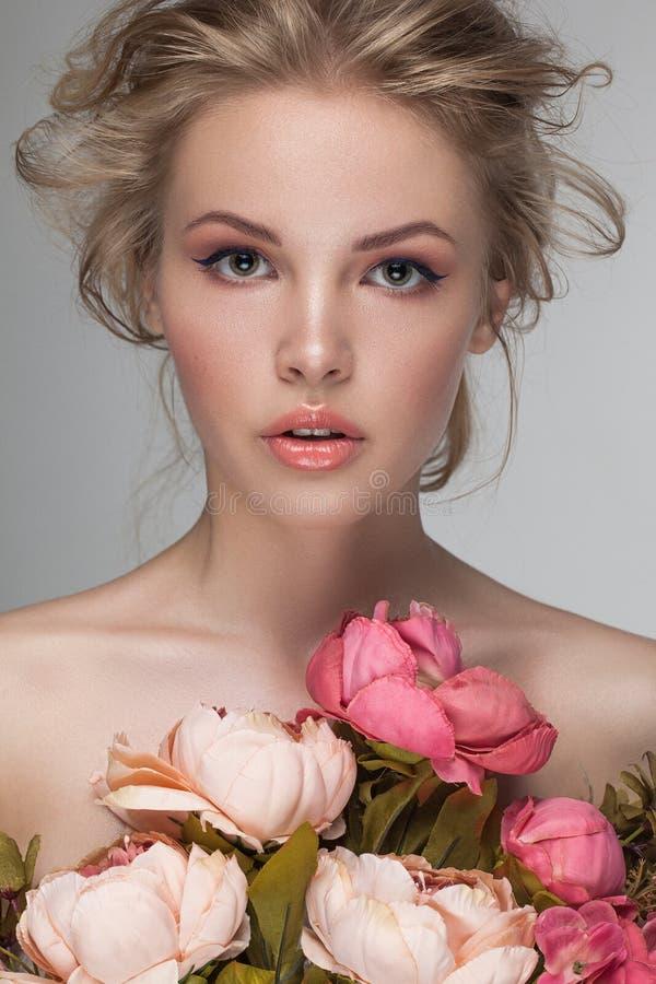 Κινηματογράφηση σε πρώτο πλάνο πορτρέτου μιας νέας όμορφης ξανθής γυναίκας με τα φρέσκα λουλούδια στοκ φωτογραφίες