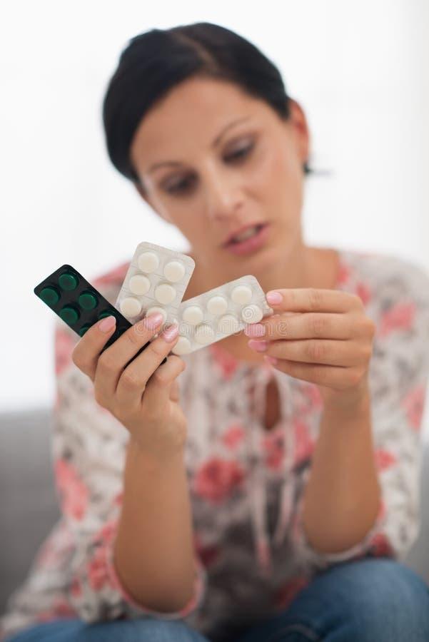 Κινηματογράφηση σε πρώτο πλάνο στα χάπια στη διάθεση της ενδιαφερόμενης νέας γυναίκας στοκ φωτογραφία με δικαίωμα ελεύθερης χρήσης
