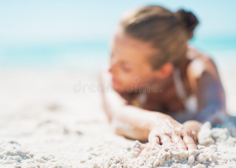 Κινηματογράφηση σε πρώτο πλάνο στη χαλαρωμένη νέα γυναίκα στο μαγιό που βάζει στην αμμώδη παραλία στοκ εικόνα