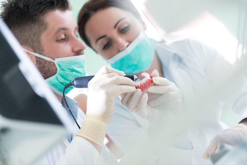 Κινηματογράφηση σε πρώτο πλάνο της άσκησης σπουδαστών οδοντιατρικής σε ένα ιατρικό μανεκέν στοκ εικόνες