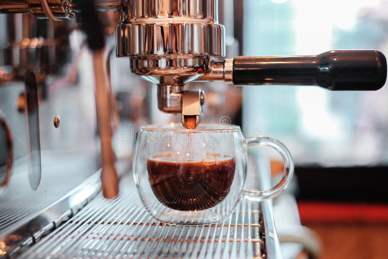 Κινηματογράφηση σε πρώτο πλάνο της έκχυσης espresso από τη μηχανή καφέ Επαγγελματικό γ στοκ φωτογραφίες