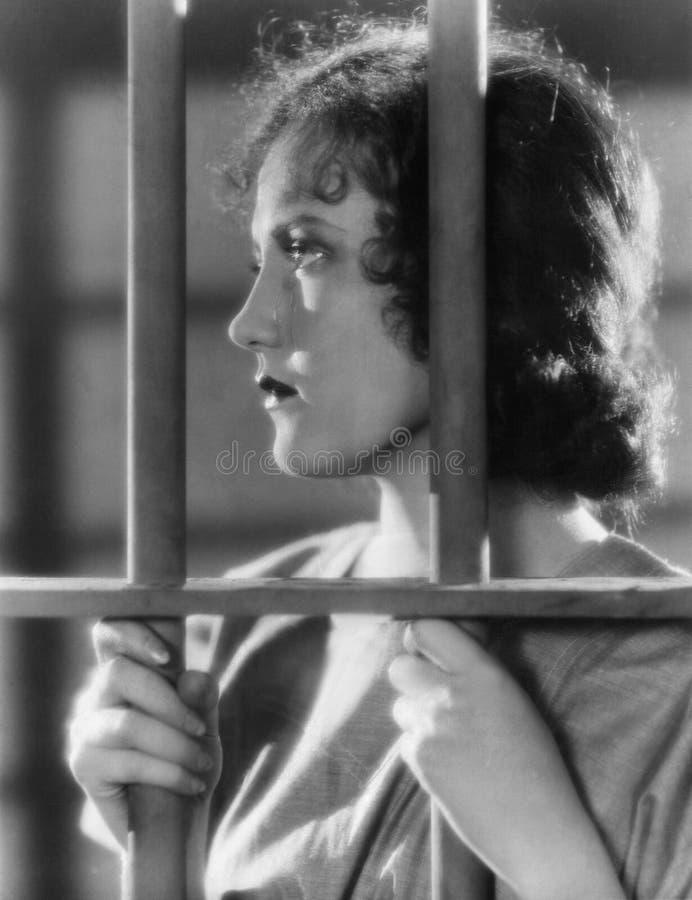 Κινηματογράφηση σε πρώτο πλάνο της γυναίκας πίσω από τα κάγκελα στοκ φωτογραφία