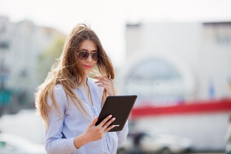 Κινηματογράφηση σε πρώτο πλάνο της ευτυχούς επιτυχούς επιχειρηματία στα γυαλιά ηλίου που χρησιμοποιούν το PC ταμπλετών στοκ φωτογραφία με δικαίωμα ελεύθερης χρήσης