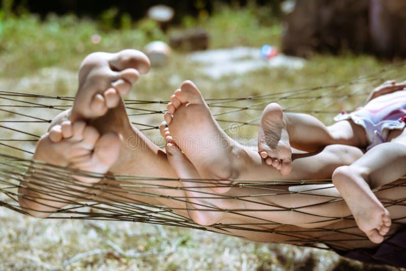 Κινηματογράφηση σε πρώτο πλάνο της ευτυχούς οικογένειας που βρίσκεται στην αιώρα χωρίς παπούτσια στοκ φωτογραφίες