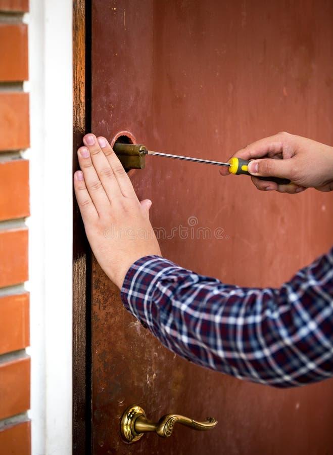 Κινηματογράφηση σε πρώτο πλάνο της κλειδαριάς πορτών καθορισμού ξυλουργών με το κατσαβίδι στοκ εικόνα με δικαίωμα ελεύθερης χρήσης