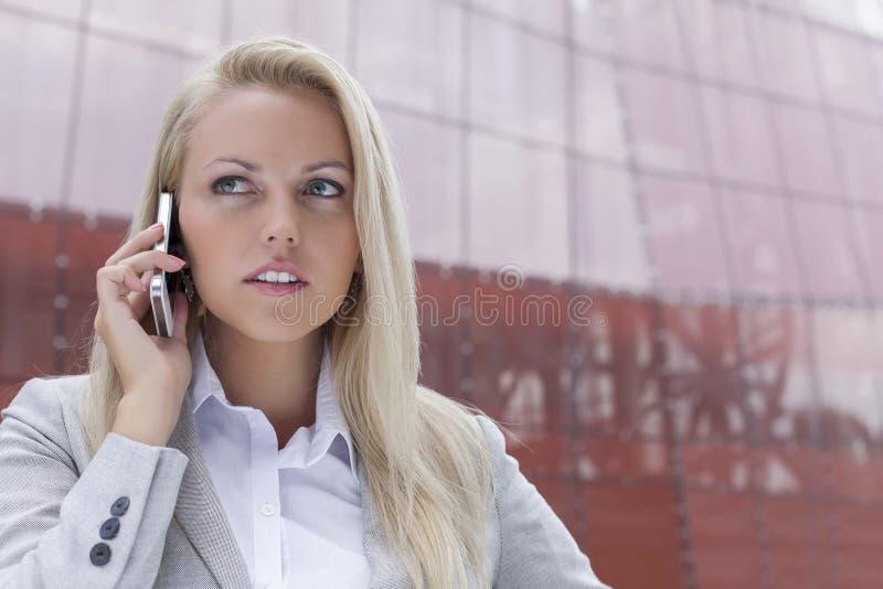 Κινηματογράφηση σε πρώτο πλάνο της νέας επιχειρηματία που επικοινωνεί στο κινητό τηλέφωνο ενάντια στο κτίριο γραφείων στοκ φωτογραφίες