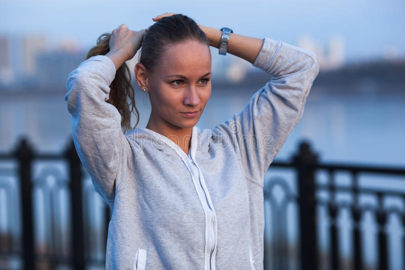 Κινηματογράφηση σε πρώτο πλάνο της νέας θηλυκής δένοντας τρίχας αθλητών πριν από ένα τρέξιμο στοκ εικόνες