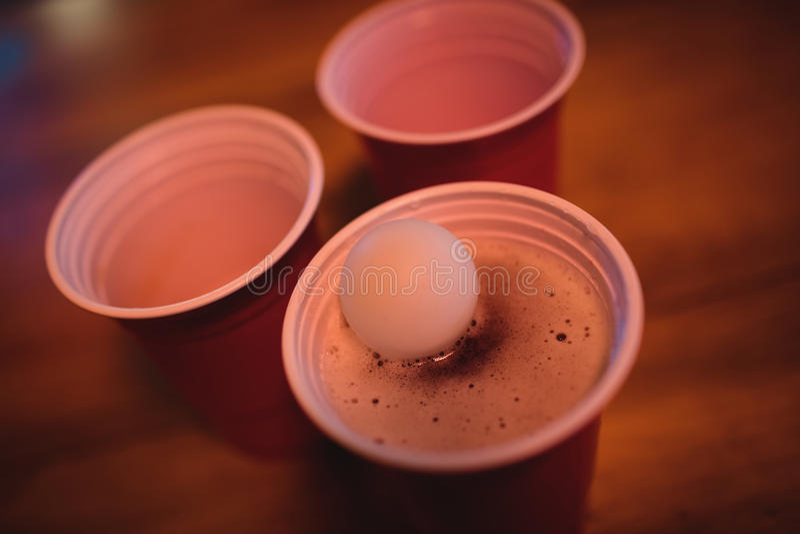 Κινηματογράφηση σε πρώτο πλάνο της σφαίρας pong στο γυαλί μπύρας στοκ φωτογραφίες