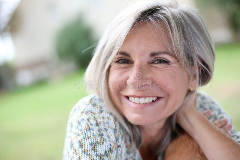 Κινηματογράφηση σε πρώτο πλάνο της χαμογελώντας ώριμης γυναίκας υπαίθριας στοκ φωτογραφίες